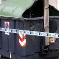 Un contenedor quemado en una calle de una ciudad