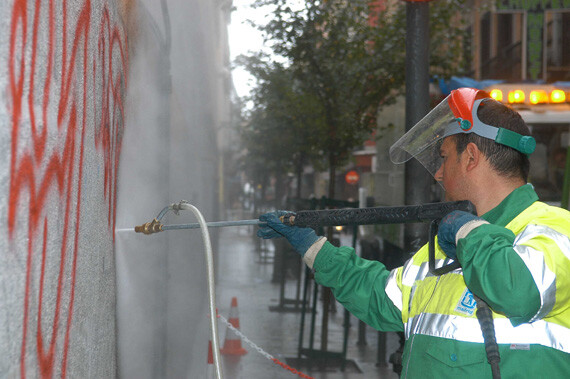 Un operario limpia unas pintadas de una pared/espormadrid
