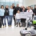 Varios miembros de 'Alma de Acero' entregando el cheque y la silla eléctrica a la AECC