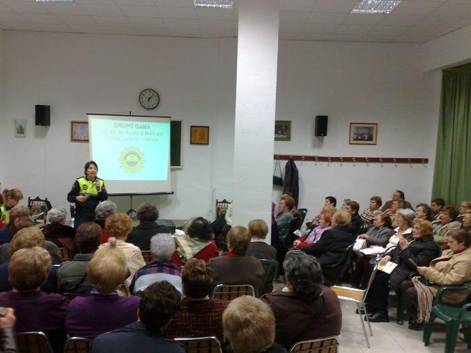 Una agente pronuncia una charla a un grupo de mujeres/plv