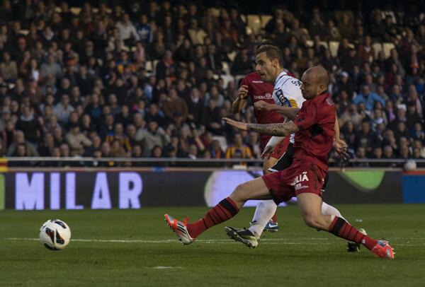 El capitán del Valencia CF dispara ante la oposición de un defensa rival. Foto: Isaac Ferrera