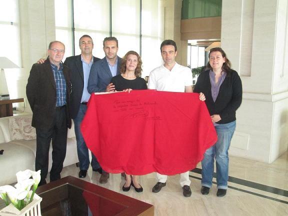 Enrique Ponce sostiene el capote con miembros de la cofradía de Medinaceli del Grao/medinaceli