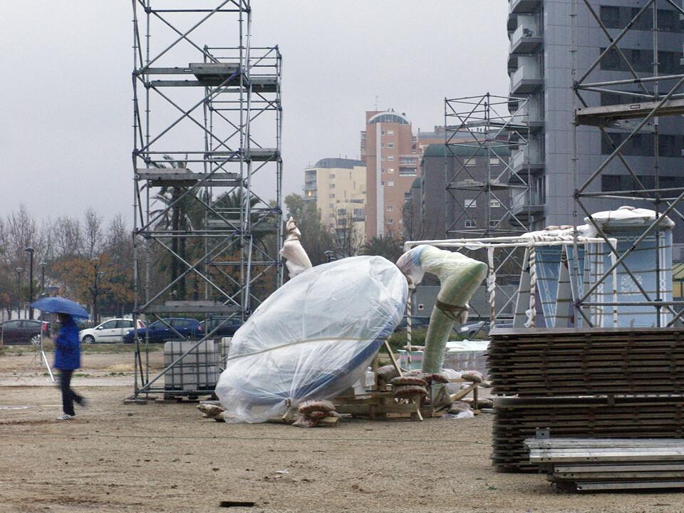 Un hombre se refugia de la lluvia con un paraguas mientras los plásticos tapan los naipes de Nou Campanar/manuel molines