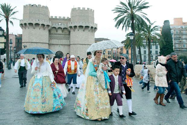 Falleras protegidas con paraguas vuelven de la Ofrenda. Foto: Manuel Guallart