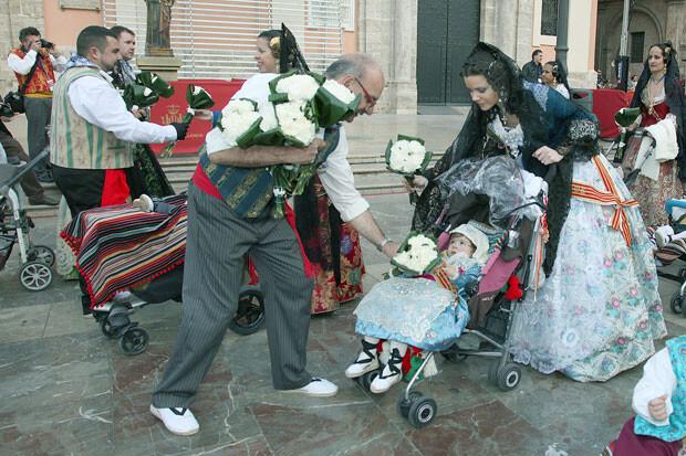 Los 'vestidors' de la Virgen recogen los primeros ramos de flores de la Ofrenda 2013. Foto: Manolo Guallart