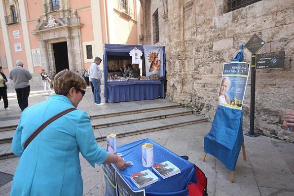 Un mujer deposita un donativo para financiar la escultura del beato Juan Pablo II/javier peiró