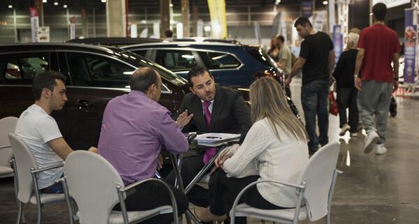 Una pareja atiende las explicaciones de un vendedor en la feria del vehículo de ocasión/Isaac Ferrera