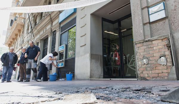 En primer plano daños del fuego y al fondo una mujer limpia los restos delante de la oficina de Bankia/I.Ferrera