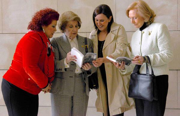 Consuelo Císcar y Mª José Catalá ojean el libro junto a la viuda y la autora del mismo.