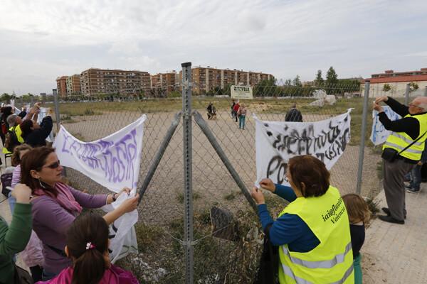 Los participantes en la protesta colocan las pancartas en las vallas del solar que quiere ceder el ayuntamiento/manuel molines