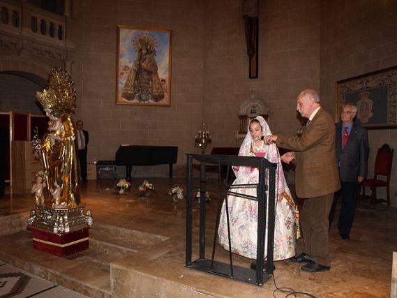 El presidente de los Seguidores sostiene el micrófono a una fallera en la capilla de la Escolanía/artur part