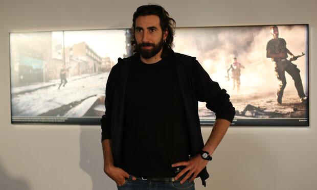El fotógrafo posa ante una de sus fotos expuestas en PhotOn 2013. Manu Brabo en PhotOn 2013. Foto: JC Barberá