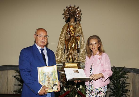 Baltasar Bueno y la edil de Cultura, Mayren Beneyto, con el libro en las manos ante la imagen de la patrona/ayto vlc