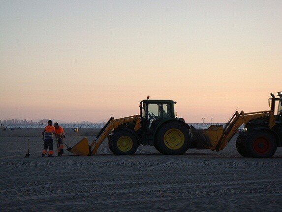 Dos operarios retiran residuos de la playa/ayto vlc