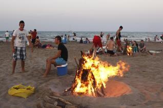 Unos jóvenes realizan unas hogueras en la playa del Cabanyal