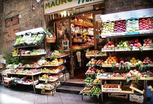 Una tienda con expositores de fruta y verduras en la calle