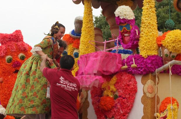 Carla González, Fallera Mayor Infantil 2013, es ayudada a ocupar su lugar en la carroza ' class=