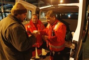 Dos voluntarios de Cruz Roja ayudan a una persona necesitada