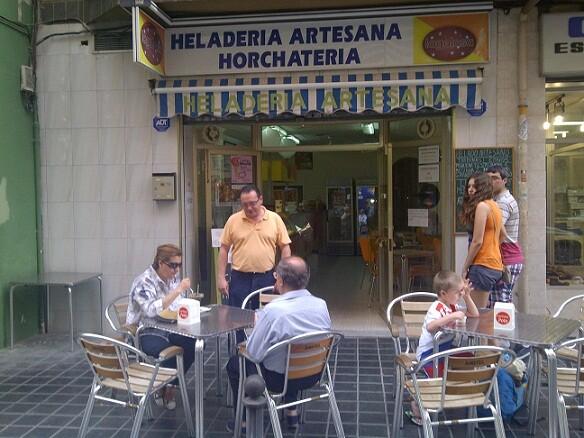 El heladero atiende a unos clientes en la puerta del local/p.varea