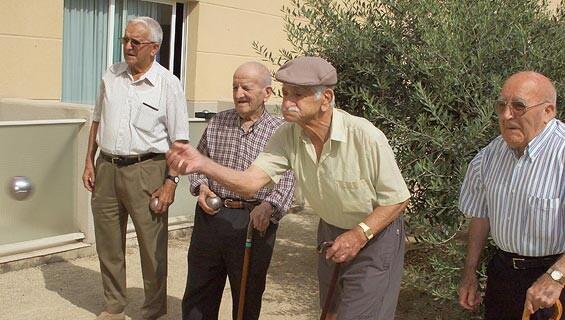 Un grupo de personas mayores juega a la petanca