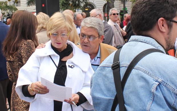 Dos ciudadanos leen el manifiesto que repartió la AVTCV en su concentración, el lazo negro ya prendido en su pecho. Foto: Javier Furió