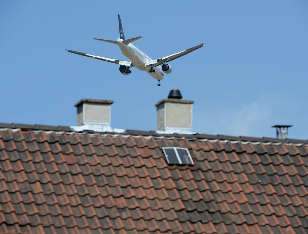 Un avión sobrevuela unas viviendas ©BELGA_DPA_A.Dedert