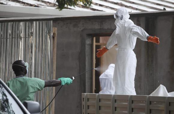 Personal médico es desinfectado después de tratar contagiados de ébola. / Efe