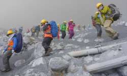 Climbers descend Mt. Ontake, which straddles Nagano and Gifu prefectures, to evacuate as volcanic ash falls at the mountain, central Japan