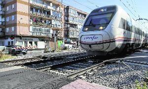 Un tren cruza el paso a nivel de Pilarica mientras un vehículo espera con la barrera bajada. :: Andrea Breiz