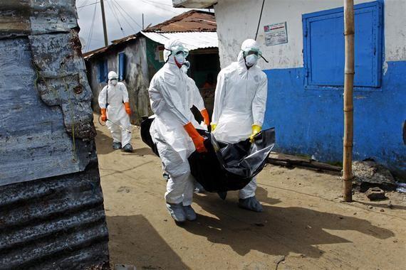 Trabajadores de la salud en Liberia recogen el cuerpo de una víctima de ébola en West Point (Monrovia)