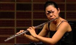 Flautista toca una sonata con mariposa en la cara
