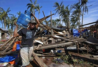 A typhoon victim carries a gas tank for cooking past a house destroyed by Typhoon Hagupit in Borongan city, Samar