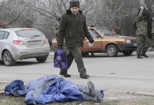 En la ciudad de Mariúpol un hobre pasa cerca de un cadáver. (Foto-Agencias)