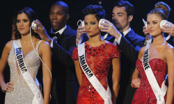 Vega, Fennell, and Harkusha are seen with headphones during a question phase of the 63rd Annual Miss Universe Pageant in Miami