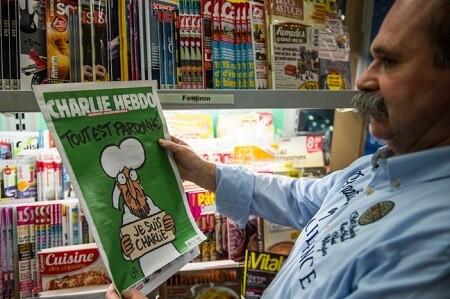 Un lector con el número especial de la revista satírica. (Foto-AFP)