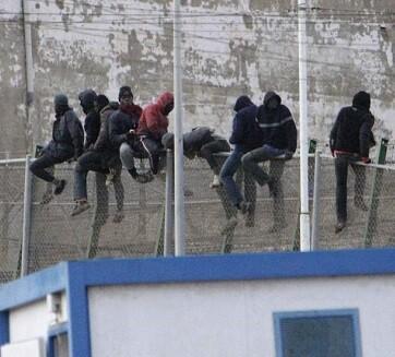 Inmigrantes encaramados a la valla que hasta esta madrugada se mantenían ahí. (Foto-rtve)