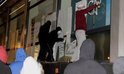 Manifestantes realizando una pntada en la fachada de un banco. (Foto-Valencia Noticias)
