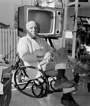 Pablo Ruíz Picasso fotografiado con una tv de fondo, uno de sus referentes en los años 60' class=