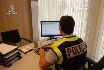 Un agente de la Policía Nacional especializado en delitos informáticos, realizando una investigación.