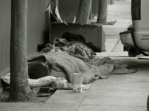 Una persona indigente duerme en la calle. Foto de archivo