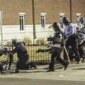 Police officers respond to a fellow officer hit by gunfire outside the Ferguson Police Headquarters in Ferguson