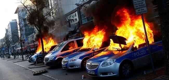 Coches de la policía quemados durante los violentos enfrentamientos. (Foto-AFP).