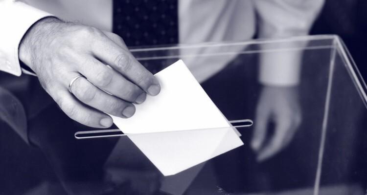 Una persona deposita su voto en una urna.