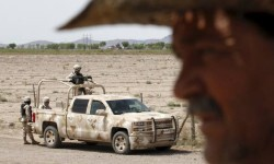A resident looks on as a soldier stands guard atop a vehicle along a road where Juarez Cartel leader Aguayo was detained on Friday by Federal troops in Villa Ahumada