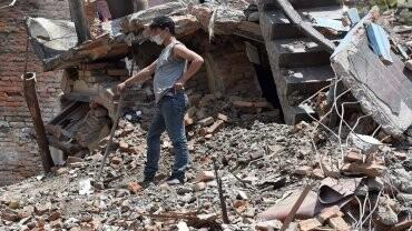 Un hombre intenta recuperar alguno de los cadáveres que se encuentran entre las ruinas.