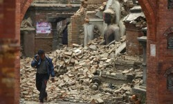 A man cries as he walks on the street while passing through a damaged statue of Lord Buddha a day after an earthquake in Bhaktapur, Nepal April 26, 2015. Rescuers dug with their bare hands and bodies piled up in Nepal on Sunday after the earthquake devastated the heavily crowded Kathmandu valley, killing at least 1,900, and triggered a deadly avalanche on Mount Everest.  REUTERS/Navesh Chitrakar
