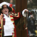 A ceremonial town crier announces the birth of a baby girl to royal fans and members of the media outside the entrance to the Lindo wing of St Mary's Hospital in London