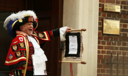 A ceremonial town crier holds a scroll after announcing the birth of a baby girl to royal fans and members of the media outside the entrance to the Lindo wing of St Mary's Hospital in London