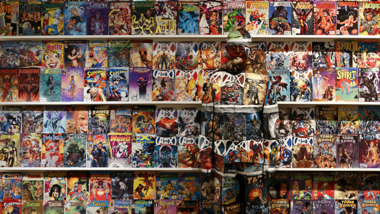 "Liu Bolin, a Chinese artist, blends himself into the background in front of a shelf lined with comic books as part of a series of performances in Caracas, Venezuela, in this November 2, 2013 file photo.    REUTERS/Jorge Silva/Files FROM THE FILES PACKAGE ""OPTICAL ILLUSIONS"" SEARCH ""OPTICAL ILLUSIONS"" FOR ALL 11 IMAGES"