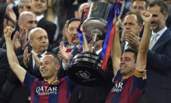 Barcelona's midfielder Xavi Hernandez (R) and Barcelona's midfielder Andres Iniesta (L) celebrate with the trophy past Spain's King Felipe VI (TopL) after the Spanish Copa del Rey (King's Cup) final football match Athletic Club Bilbao vs FC Barcelona at the Camp Nou stadium in Barcelona on May 30, 2015. Barcelona won 3-1.   AFP PHOTO/ LLUIS GENE